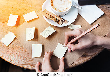 Close up of woman hands drawing different notes stickies by wooden pencil. Young beautiful woman drawing various message for a boy friend in a caffe. View from above.