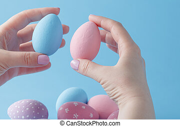 close up of woman hands holding colored easter eggs