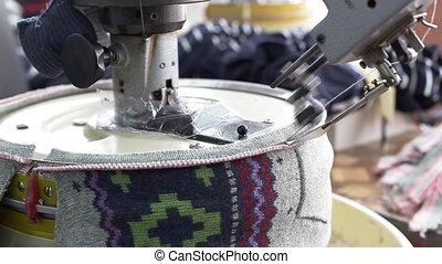 Close up of woman hands sewing an overlock at sewing machine