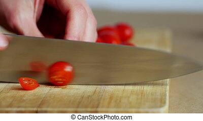 Close up of woman hands slicing cherry tomatoes, 4k