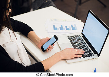 Close Up of woman hands using mobile phone and laptop computer with blank copy space screen for your advertising text message or content business.