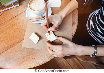 Close up of woman hands writing differents notes stickers by wooden pencil. Young beautiful woman drawing various message for a boy friend in a cafe. View from above.