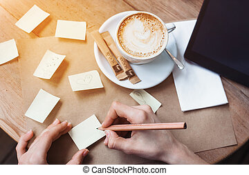 Close up of woman hands writing differents notes stickies by wooden pencil. Woman hands drawing various message or sketch. View from above. Tablet with black space screen for your advertising text message or promotional content