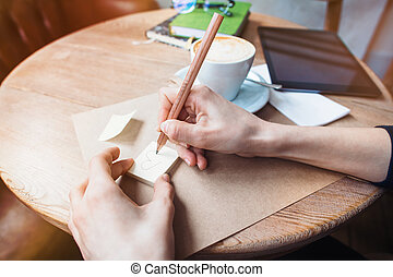 Close up of woman hands writing love notes stickers by wooden pencil. Young beautiful woman drawing love message for a boy friend in a cafe. View from above. Tablet with black space screen for your advertising text message or promotional content