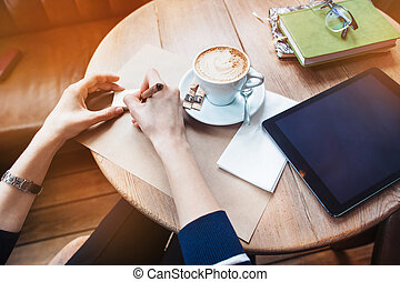 Close up of woman hands writing notes stickers by wooden pencil. Young beautiful woman writing her self schedule task in a cafe. View from above. Tablet with black space screen for your advertising text message or promotional content