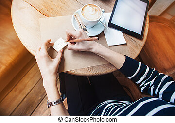 Close up of woman hands writing notes stickies by wooden pencil. Young beautiful woman writing drawing in a cafe. View from above. Tablet with blank copy space screen for your advertising text message or promotional content