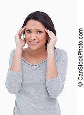 Close up of woman having a headache against a white...