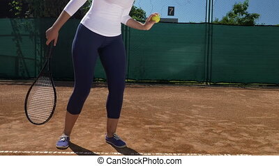 Close up of woman having a tennis racket in hand and with the other hand bouncing a ball on the cinder