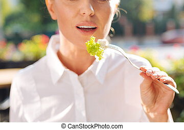 Close up of woman holding a fork with salad