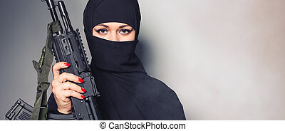 Close-up of woman holding an automatic weapon - Woman...
