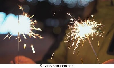 Close up of woman holding sparkler on the street