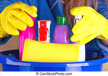 close-up of woman holdinh basin with cleaning supplies