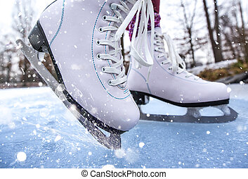Close-up of woman ice skating on a pond on a freezing winter day