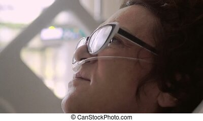 Close up of woman in aged wearing eyeglasses lies in a hospital bed with an oxygen mask on a drip. 4k