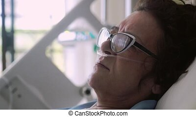 Close up of woman in aged wearing eyeglasses lies in a hospital bed with an oxygen mask on a drip. 4k.