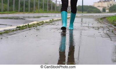 Close-up of woman in blue rubber boots jumping on the puddle...