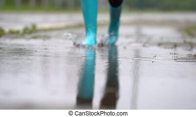 Close-up of woman in blue rubber boots jumping on the puddle