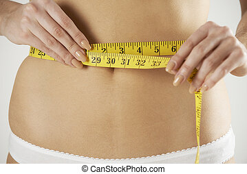 Close-Up Of Woman In Underwear Measuring Waist With Tape
