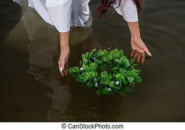 Close-up of woman in white dress in the water. Art Woman with wreath in river. Wet witch Girl in the lake