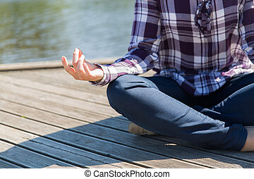 close up of woman in yoga lotus pose outdoors