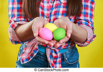 Close up of woman l holding colorful Easter eggs