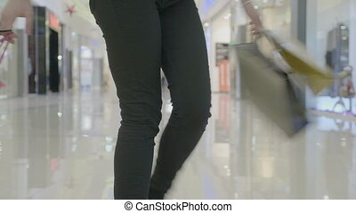 Close up of woman legs in dark trousers walking and spinning at the mall while carrying shopping bags in both hands