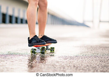 Close up of Woman Legs Riding Orange Skateboard on the Wet Road in the Rain