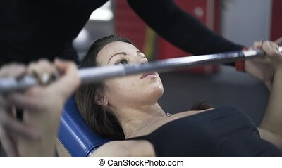Close up of woman lifting barbell with a coach