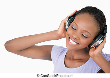 Close up of woman listening to music against a white ...