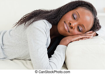 Close up of woman lying on the couch with eyes closed
