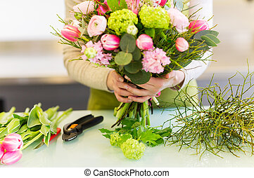 close up of woman making bunch at flower shop - people,...