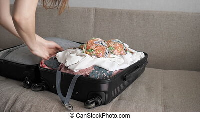 woman packing suitcase quickly - close up of woman packing...