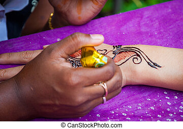 Close-up of woman painting henna tattoo