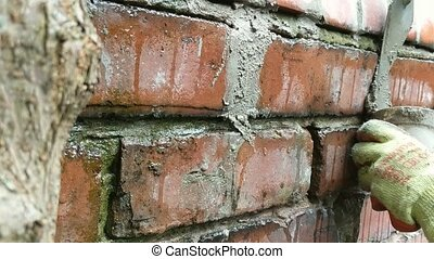 Close up of woman pointing brick wall with mortar. - Close...