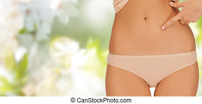 close up of woman pointing finger at her abs