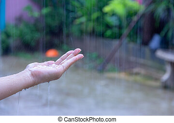 woman putting her hand in the rain catching drops of rain