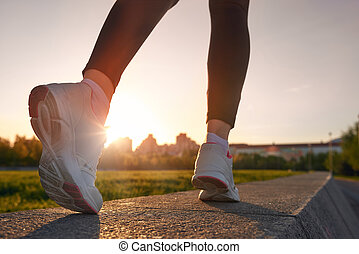 Close up of woman running shoes on sunset