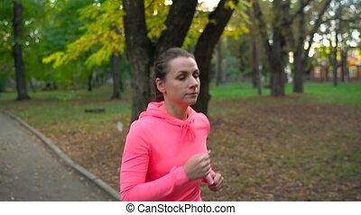 Close up of woman running through an autumn park at sunset