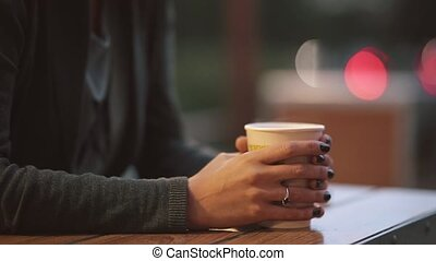 Close-up of woman s hand holding a cup of coffee, camera moving up to the girls face. Blurred lights background.