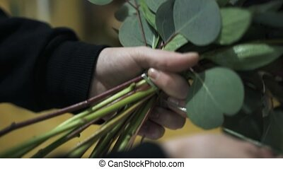 Close up of woman s hands tying a flower bouquet in her shop
