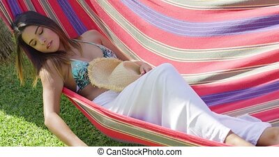 Close up of woman sleeping in hammock