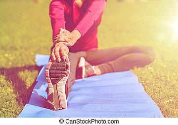 close up of woman stretching leg on mat outdoors - fitness,...