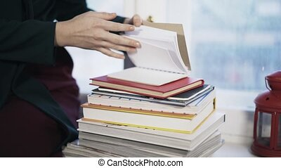 Close up of woman taking a book from a pile