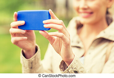 close up of woman taking picture with smartphone