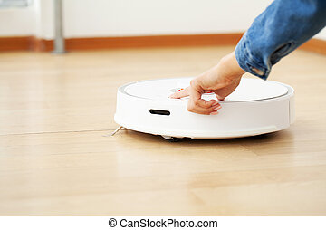 Close up of woman turns on smart robot vacuum cleaner