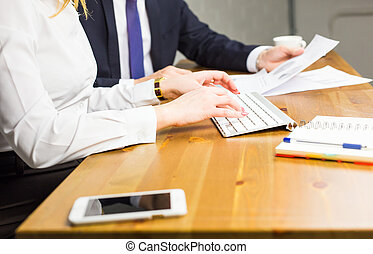 Close-up of woman typing on keyboard in office