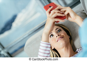 Close-up of woman using her smartphone lying on the sofa.