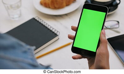 Close-up of woman using smartphone with green screen. Close-up video of woman's hands holding mobile phone. Chroma key. Vertical