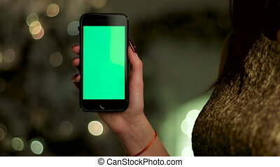 Close up of woman wearing gold dress, holding her mobile phone in hands. Green screen Chroma Key. Close up.