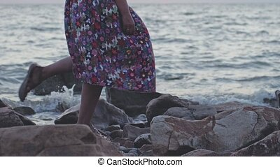 close up of woman wearing long dress walking on rocky beach in slow motion. 3840x2160